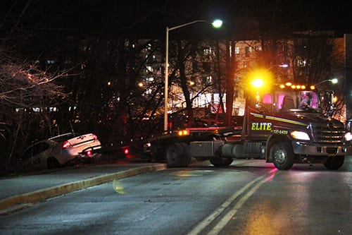 A Stony Brook Police Department cruiser is removed from a ditch near the Tabler Residence Quad after an officer struck a female student on the sidewalk. (ANUSHA MOOKERJEE / THE STATESMAN)