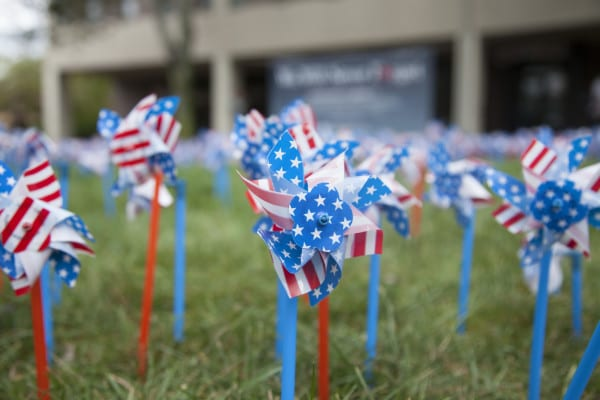 Students can stop by and place a pinwheel on the grass throughout the day. ERIC SCHMID/THE STATESMAN