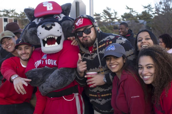 Students pose with Wolfie wearing red and showing their Stony Brook Seawolves pride during tailgating. MICHAELA KILGALLEN/THE STATESMAN